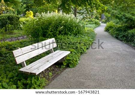 A trailside bench invites hikers to rest and enjoy the natural surroundings of The Morton Arboretum in Lisle, Illinois. - stock photo
