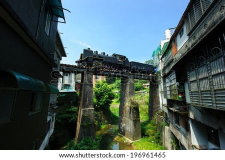 A train crossing a very old bridge through a town with old buildings. - stock photo