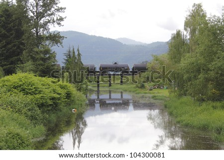 A train delivers dangerous toxic chemicals across a bridge spanning a pristine creek/Toxic Chemicals/Nature confronted by toxic dangers - stock photo