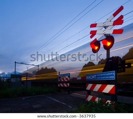 A train passing a rail crossing, surrounded by fences and barb wire on a summer evening. - stock photo