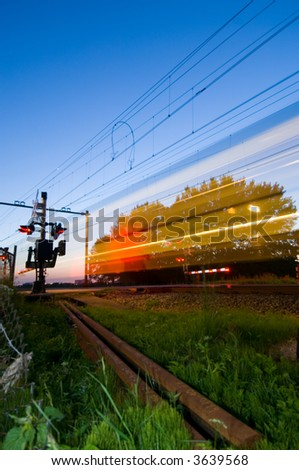 A train passing a railway crossing at night - stock photo