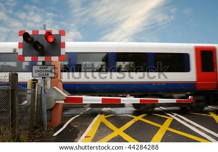 A train passing across a level crossing, on a small road. - stock photo