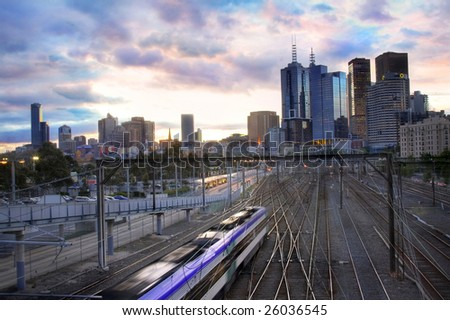 A train toward the city in a gleaming sunset - stock photo