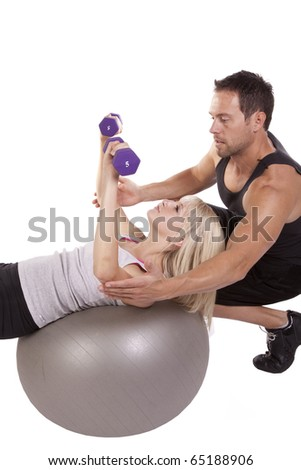 A trainer helping the woman use the weights while laying back on the ball. - stock photo