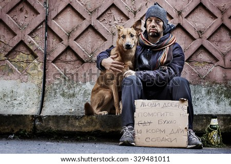 "A tramp and his dog with sad faces are cadging with a plate. On the plate is written on russian language ""Please give me some money for alcohol and dog food"" . Image with toning and selective focus - stock photo"