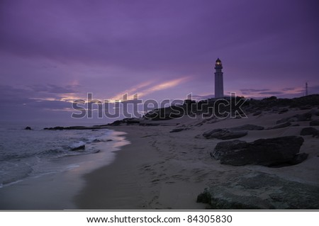 A tranquil beach with a purple sunset with a lighthouse in the background - stock photo