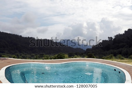 A tranquil blue jacuzzi spa pool on a green hillside environment for the concept of paradise oasis. - stock photo