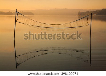 A tranquil image of a volleyball net reflected in the still morning waters on a lake.