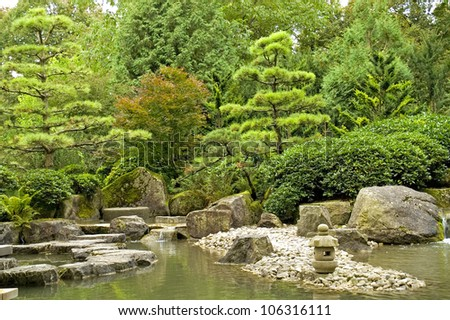 A tranquil scene with rocks, a rock lantern, water and trees in a japanese garden - stock photo