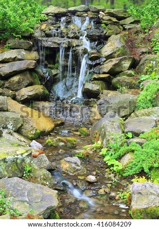 A tranquil waterfall and stream in a woodland rock garden. - stock photo