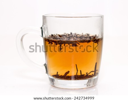 A transparent glass filled with brown leaves and yellow liquid.