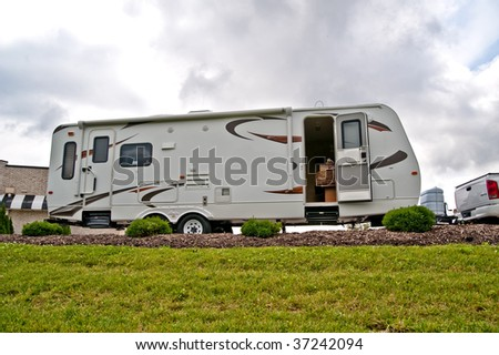 A travel trailer sits on a hill with the door open and a dog seated on the bed inside. - stock photo