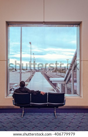 A traveler is looking at the airport through the window. - stock photo