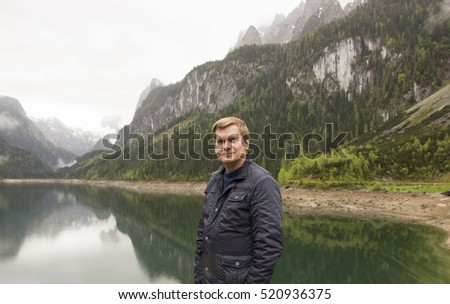 A traveler on the background of an alpine lake Gosausee in cloudy weather, Austria
