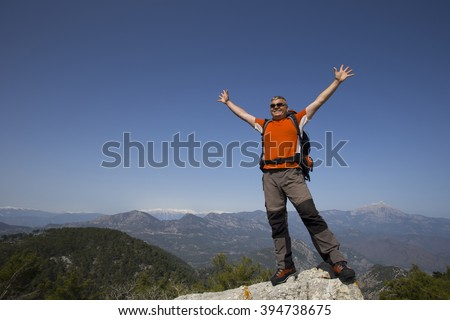 A traveler stands on top of a mountain and looks out to sea. - stock photo