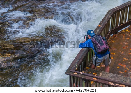 A traveller or photographer is taking pictures of a waterfall during fall foliage season, Virginia, USA - stock photo