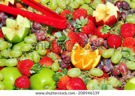 A tray filled with a variety of peeled and sliced fruits