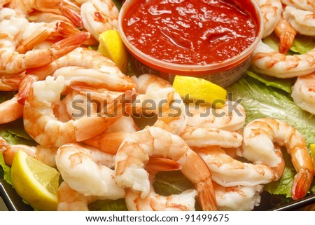 A tray of cooked shrimp with a lemon wedges and sauce - stock photo