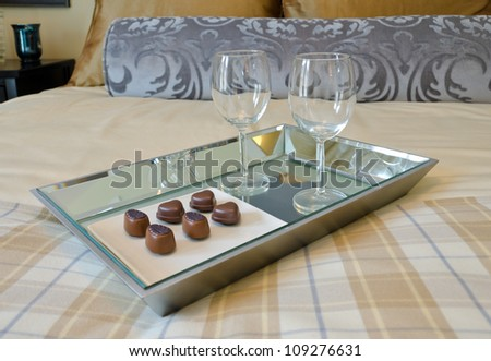 A tray on the bed with wine glasses and some chocolate candy - stock photo