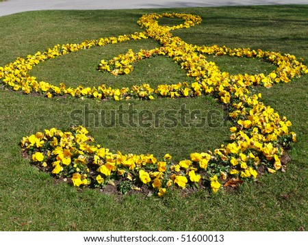 A treble clef arranged with beautiful yellow flowers - stock photo