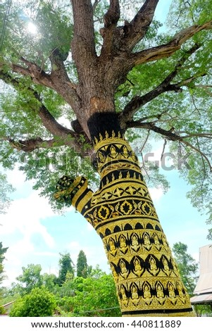A tree that decorated with gold buddhist angel and Thai kanok around the trunk. - stock photo