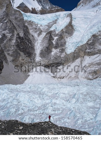 A trekker stands in front of the massive Khumbu Glacier near Everest Base Camp in Nepal. - stock photo