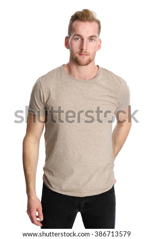 A trendy and attractive man in his 20s wearing black jeans and a tan t shirt standing against a white background in a studio. - stock photo