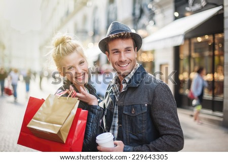 a trendy young couple walks in the city at christmastime, the young woman wears a leather jacket , shopping bags at her arm and the man a cup of coffee in hand - stock photo