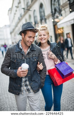 a trendy young couple walks in the city, the young woman has shopping bags at her arm and the man a cup of coffee in hand - stock photo
