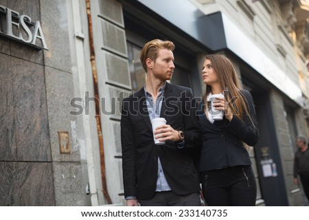 a trendy young couple walks in the city with a cups of coffee in their hands - stock photo