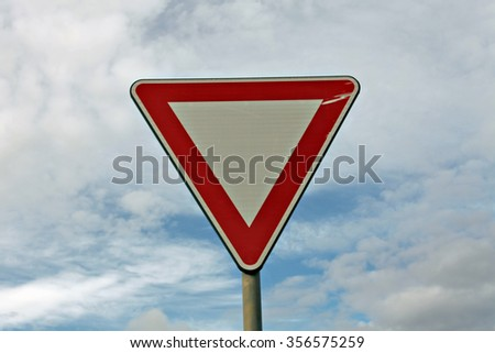 """A triangular road sign in Italy's countryside, meaning """"warning"""". Shot against a cloudy sky.  - stock photo"""