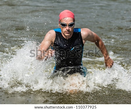 A triathlete is running out of the water