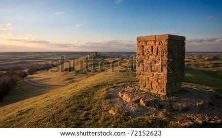 A trig point at Burton Dassett country park, overlooking the Warwickshire countryside at sunset.