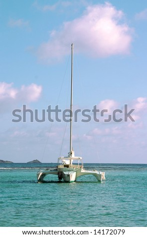 A Trimaran sailboat anchored in the bay of a paradise island setting.
