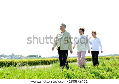 A trio of elderly women walk on the green hills