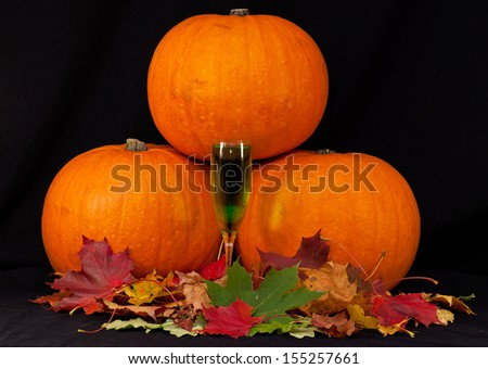 A trio of pumpkins with glass of green poison against a black background. - stock photo
