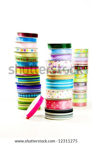 A trio of stacks of brightly colored ribbon on a white background. - stock photo