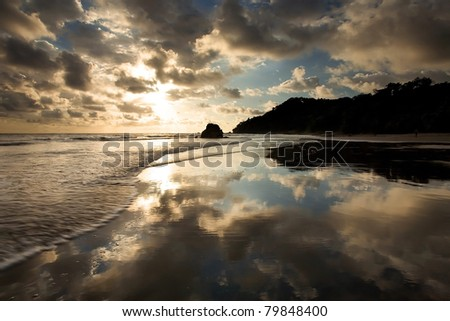 A tropical beach at sunset in Costa Rica, with waves and perfect reflection - stock photo