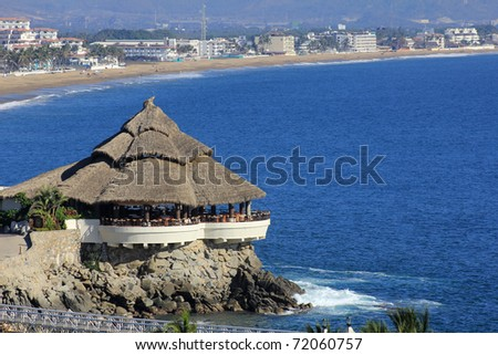 A tropical cabana on a rock jetty by the beach and ocean - stock photo