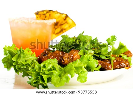 A tropical, fruity drink with a plate of barbecue buffalo chicken wings.