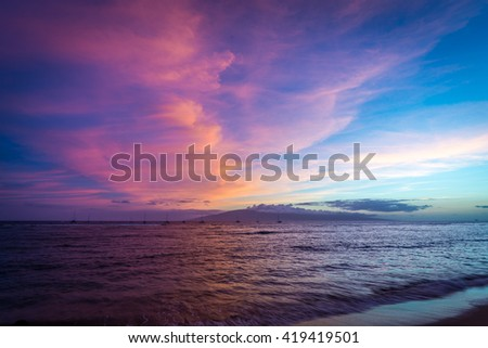 A tropical island at sunset with amazing clouds in the sky. - stock photo