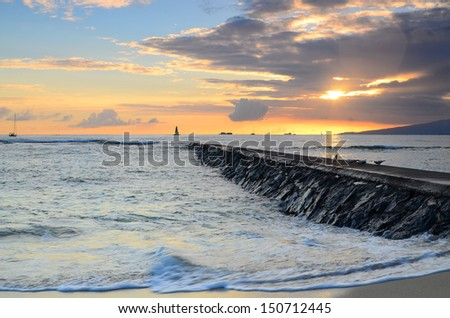 A tropical sunset on the beach in Waikiki, Hawaii with a rock jetty in the foreground. - stock photo