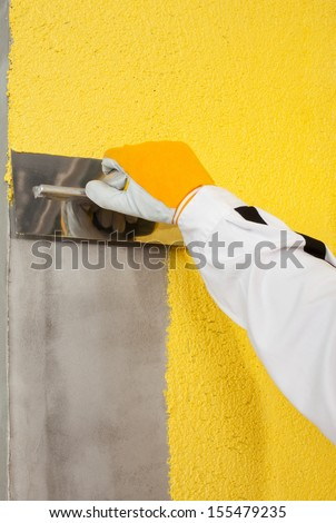 A trowel spreading a plaster on a corner-wall - stock photo
