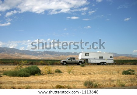 A truck pulls along a motor-home trailer. - stock photo