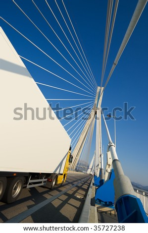 A truck through the pylons of suspension of a bridge. You can use the side of trucks to insert a text - stock photo