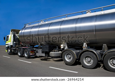 A truck with a big tank for delivering liquid cargoes. - stock photo