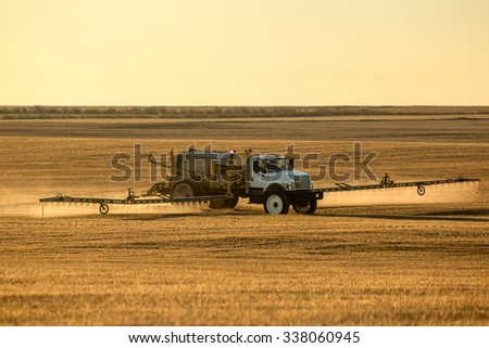 A truck with booms out spraying a field preparing it to plant wheat on a farm in the early morning. - stock photo