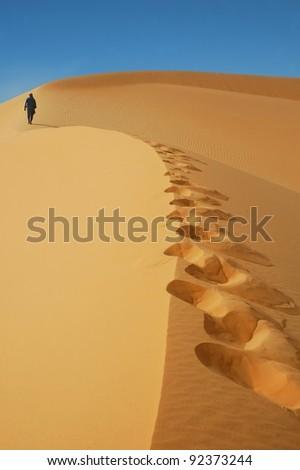A Tuareg man walking up a sand dune in the Sahara desert - stock photo