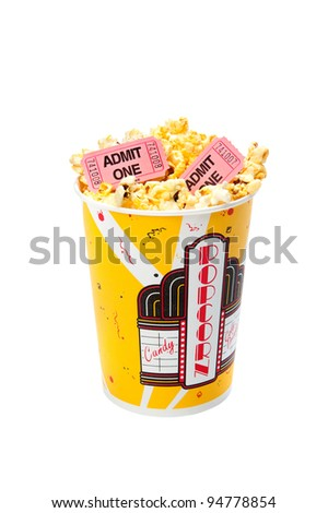 A tub of popcorn with movie tickets on top. - stock photo