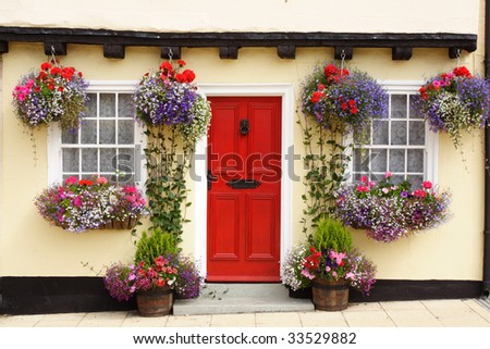 A Tudor cottage, with a beam and bright red door, has colorful hanging baskets and window boxes. - stock photo